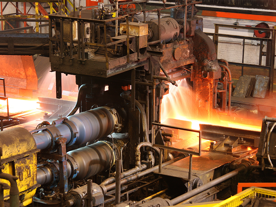 Hot steel being rolled to shape in mill in steel manufacturing p